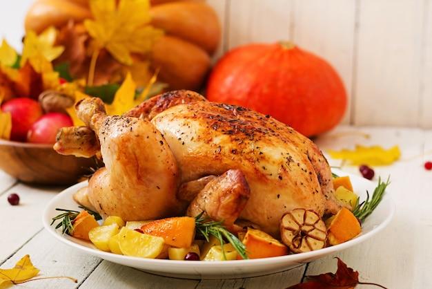 Tacchino arrosto guarnito con mirtilli rossi su un tavolo in stile rustico decorato con zucche, arance, mele e foglie d'autunno.