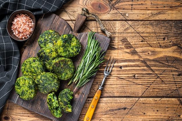 Broccoli vegetariani arrosto e tortino o cotoletta di verdure di piselli, falafel. fondo in legno. vista dall'alto. copia spazio.