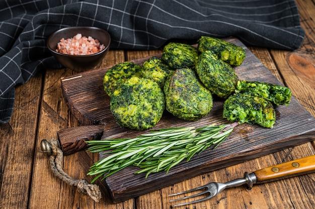 Broccoli vegetariani arrosto e tortino o cotoletta di verdure di piselli, falafel. fondo in legno. vista dall'alto.