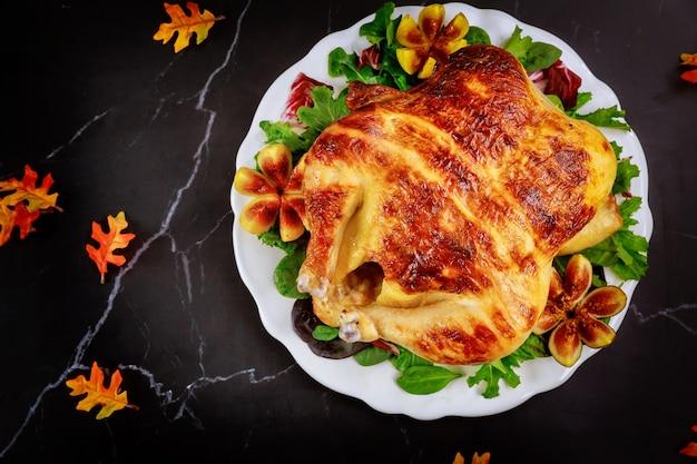 Tacchino intero arrosto con insalata su sfondo nero per il giorno del ringraziamento
