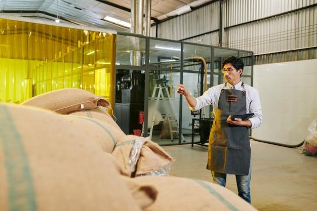 Proprietario di torrefazione con tavoletta digitale nelle mani che contano sacchi con chicchi di caffè in magazzino