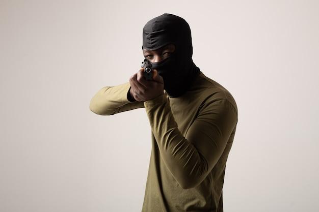 Ladro in un passamontagna con un'arma in mano su un muro bianco