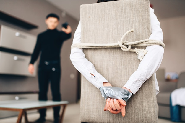 Il ladro in abiti neri spaventa la vittima legata con corda e nastro adesivo alla sedia. rapina a casa, maniaco è penetrato nell'appartamento