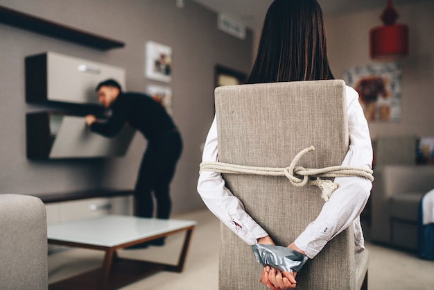 Ladro in abiti neri che perquisisce gli armadietti della casa contro la vittima di sesso femminile legata con corda e nastro alla sedia. rapina a casa, maniaco è penetrato nell'appartamento. gangster pericoloso al chiuso