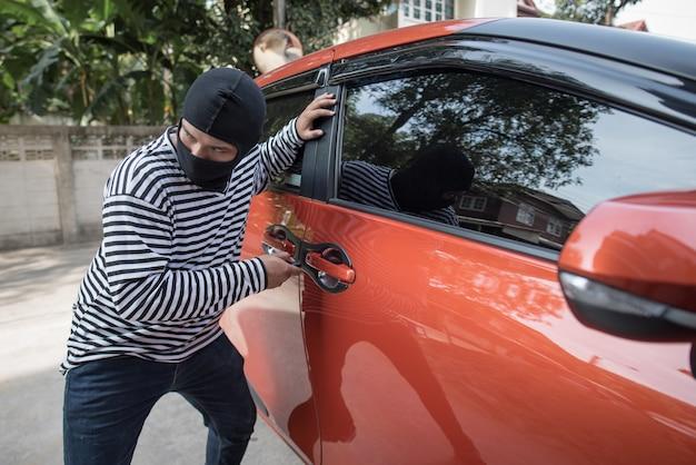 Ladro e il ladro d'auto in una maschera apre la portiera della macchina e dirotta la macchina.