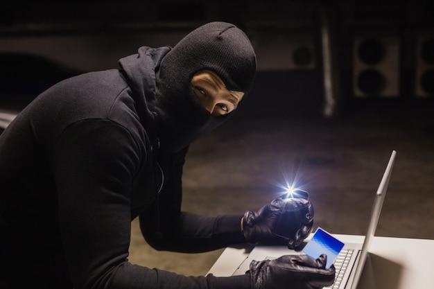 Ladro che fa acquisti online mentre fa luce