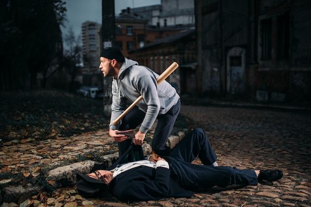 Il ladro con la mazza da baseball uccide la sua vittima e prende una borsa all'ingresso. theif commette una rapina contro un uomo. concetto di criminalità
