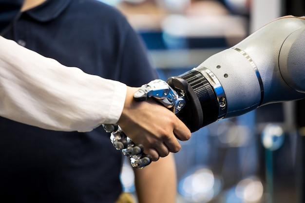 Mano del robot che agita la mano umana