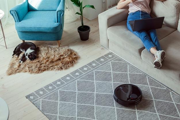 Aspirapolvere robot che pulisce tappeto, gatto, donna che usa un laptop seduto sul divano di casa