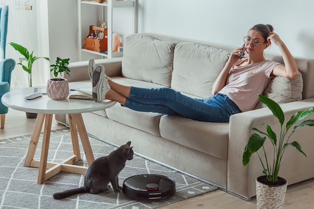 Robot aspirapolvere pulizia tappeto, donna e gatto resto seduto sul divano a casa e parla al telefono