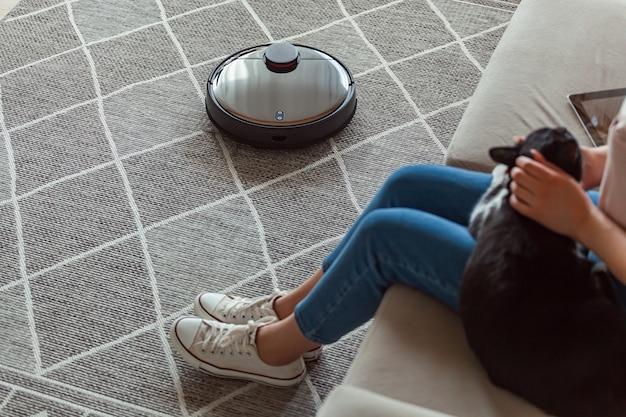 Robot aspirapolvere pulizia tappeto, donna e gatto resto seduto sul divano di casa