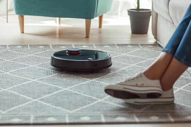 Robot aspirapolvere pulizia tappeto, gambe di donna riposano seduto sul divano di casa