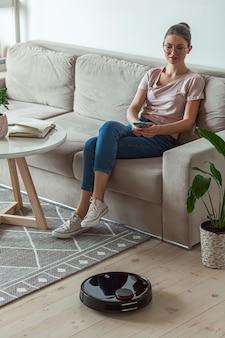 Robot aspirapolvere pulizia tappeto, donna telecomando cellulare e godersi il riposo, seduti sul divano di casa