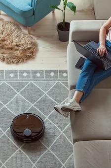 Robot aspirapolvere pulizia tappeto, donna con laptop seduto sul divano di casa