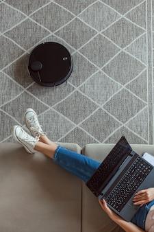 Aspirapolvere robot che pulisce il tappeto, donna che usa il portatile seduta sul divano di casa