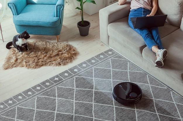 Robot aspirapolvere pulizia tappeto, donna con laptop seduto sul divano