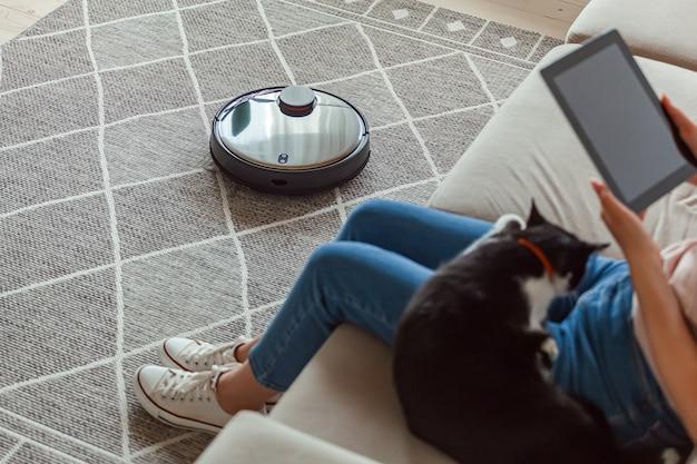 Robot aspirapolvere pulizia tappeto, donna che utilizza tablet e gioia resto e gatto seduto sul divano di casa