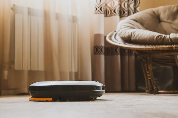 L'aspirapolvere robot in una stanza in un nuovo appartamento pulisce il pavimento in laminato. concetto di compiti e tecnologia.
