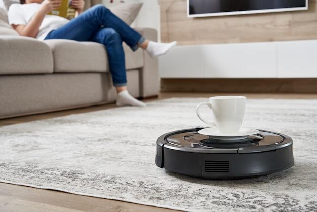 Aspirapolvere robot che porta tazza di caffè ad una donna mentre sta riposando sul divano Foto Premium