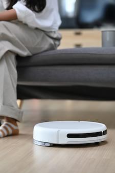 Aspirapolvere robotico che pulisce il soggiorno e la donna seduta sul divano di casa
