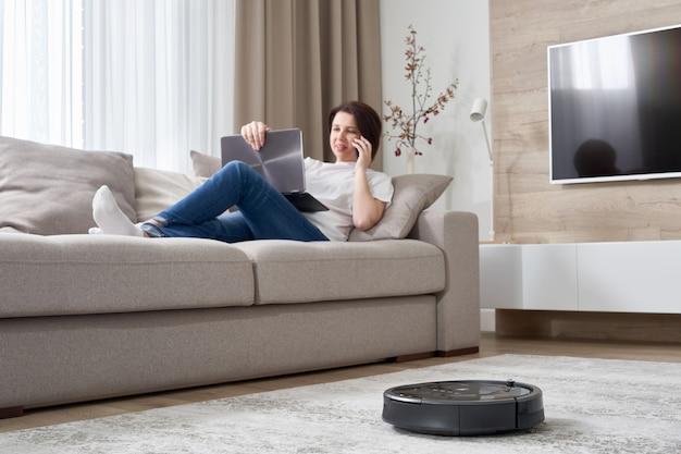 Aspirapolvere robot che pulisce la stanza mentre donna che riposa sul sofà
