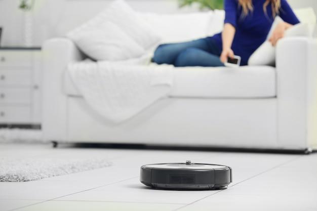 Aspirapolvere robot che pulisce la stanza mentre la donna riposa sul divano