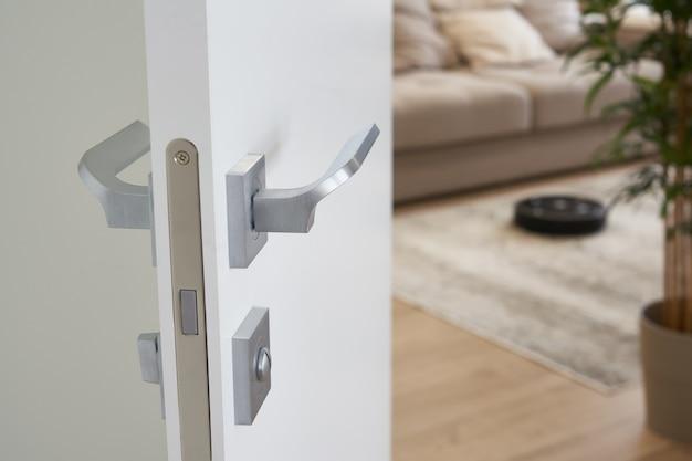 Aspirapolvere robot sul pavimento in un accogliente salotto moderno, vista attraverso la porta aperta