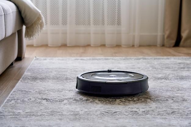 Aspirapolvere robot sul pavimento in un accogliente salotto moderno