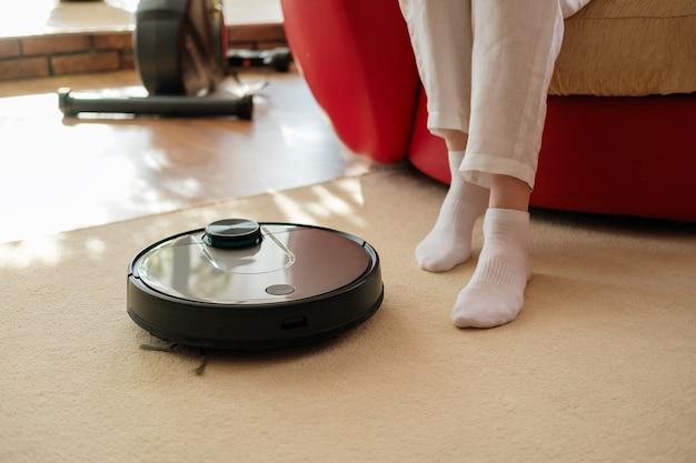 Aspirapolvere robot e gambe sul tappeto, casa pigra e confortevole, concetto di vita lenta, riposo