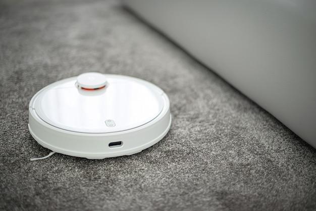 Robot aspirapolvere sul tappeto in soggiorno per la pulizia di peli di animali domestici e polvere. robot aspirapolvere che lavora su una superficie in moquette.