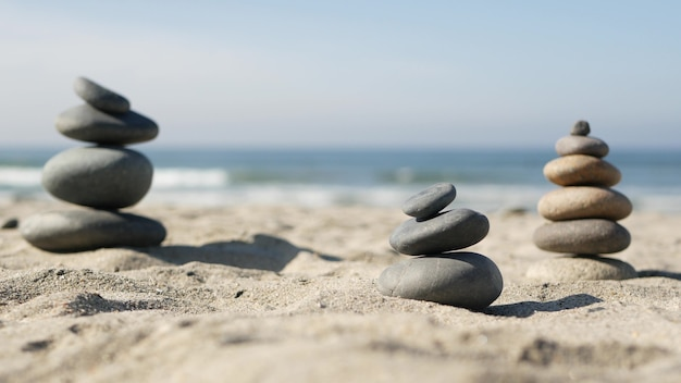 Bilanciamento della roccia sulla spiaggia dell'oceano, pietre impilate dalle onde dell'acqua di mare. piramide di ciottoli sulla riva sabbiosa. mucchio o mucchio stabile con messa a fuoco morbida con bokeh, primo piano. equilibrio zen, minimalismo, armonia e pace
