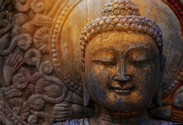 Statua del buddha della roccia con luce solare usata per gli amuleti della religione di buddismo.