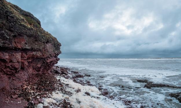 Una scogliera di roccia sopra l'acqua con un litorale di marea. mare bianco. vista panoramica.