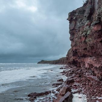 Una scogliera di roccia sopra l'acqua con un litorale di marea. mare bianco.