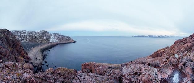 Una scogliera di roccia sopra l'acqua con un litorale di marea. meraviglioso paesaggio montano panoramico sul mare di barents. terreno geologico complesso. penisola di kola
