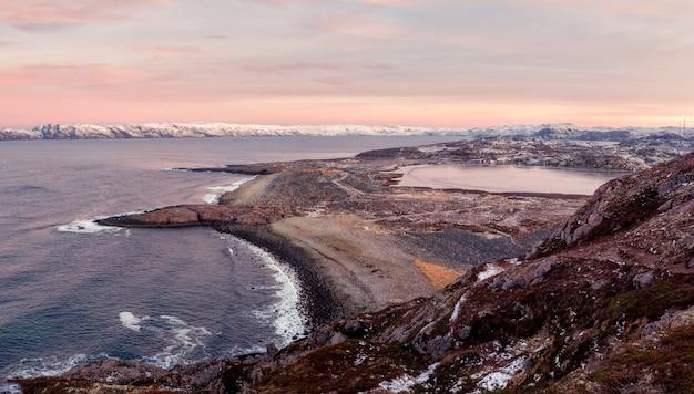 Una scogliera di roccia sopra l'acqua con un litorale di marea. meraviglioso paesaggio montano panoramico sul mare di barents. terreno geologico complesso.