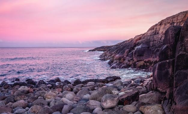 Una scogliera di roccia sopra l'acqua con un litorale di marea. meraviglioso paesaggio montano panoramico sul mare di barents. teriberka. russia.