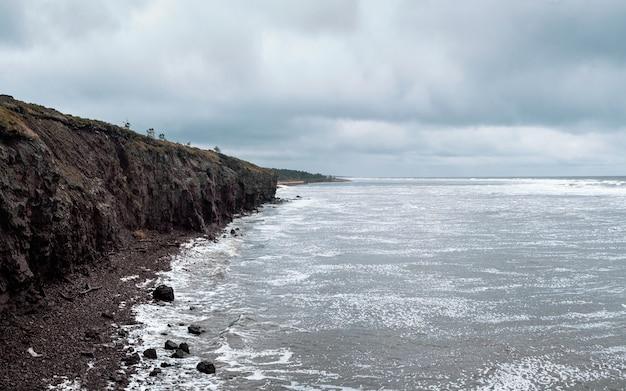 Una scogliera di roccia sopra l'acqua con un litorale di marea