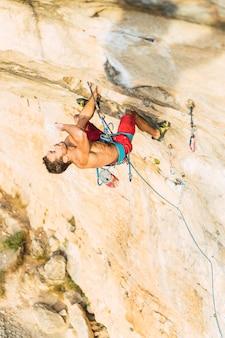Scalatore appeso alla corda cercando e pensando alla sua prossima mossa. scalatore a torso nudo che si arrampica su una parete rocciosa.