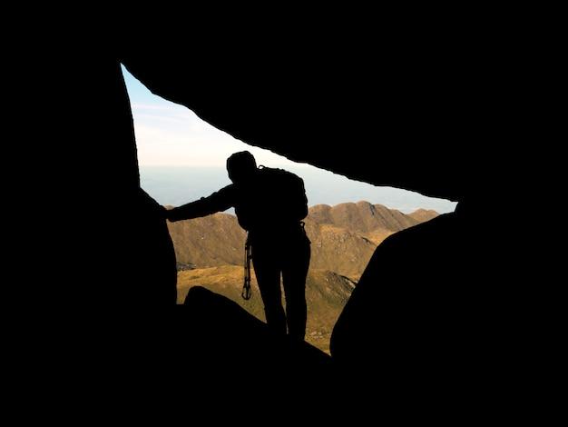 Siluetta dello scalatore dentro le rocce con le montagne