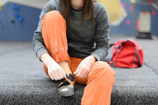 Scalatore di roccia donna seduta si toglie le scarpe rocciose su una parete di arrampicata boulder