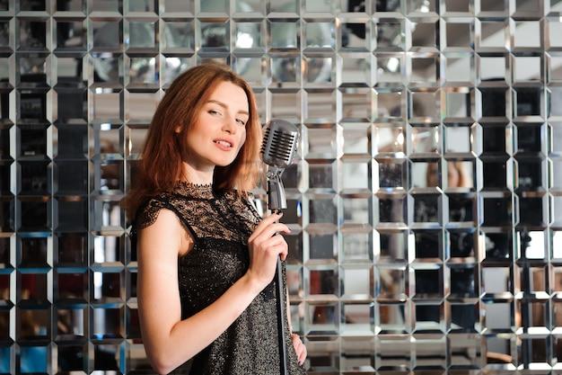 Stella del rock. ragazza sexy che canta nel retro microfono.
