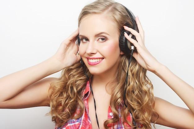 Donna di stile rock con le cuffie che ascolta la musica