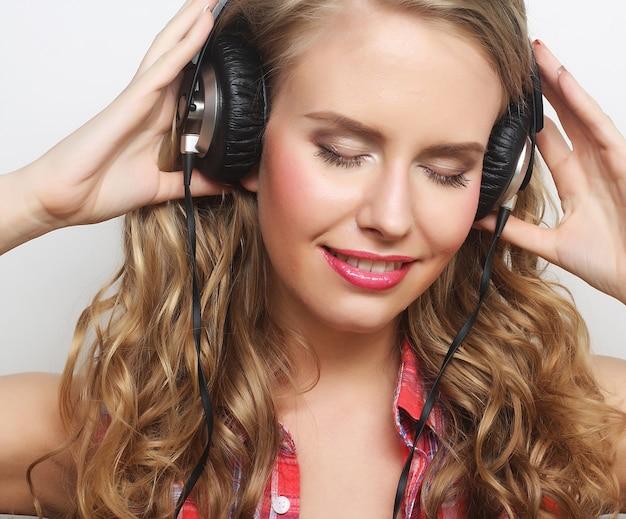 Donna in stile rock con le cuffie che ascolta la musica