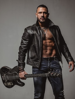Scatena questa festa. maschio sexy atletico muscolare con la chitarra. uomo brutale fiducioso e bello suona musica. festa per adulti. festa da ballo musicale. muovi il tuo corpo. goditi un suono perfetto. concetto di musicista rock.