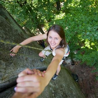 Rockclimber che aiuta lo scalatore femminile a raggiungere la cima della montagna