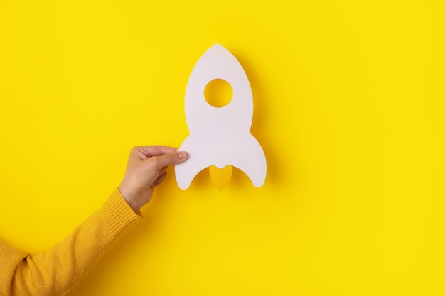 Razzo in mano su sfondo giallo, idea imprenditoriale di avvio