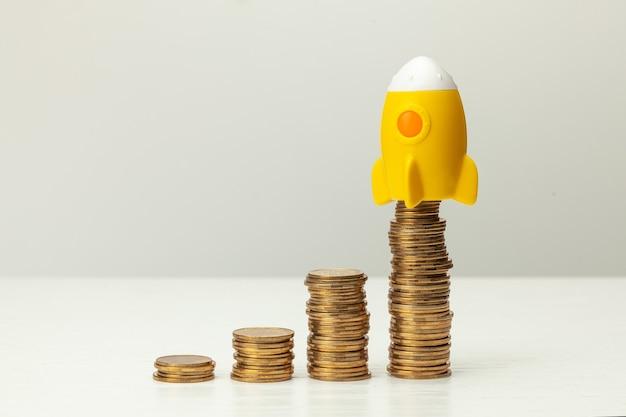Razzo e pila di monete d'oro su sfondo grigio. concetto di crescita del profitto.