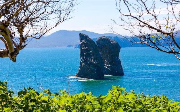 Rocce nella baia solare blu di avacha nell'oceano pacifico,