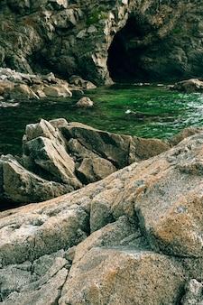 Rocce e grotte in riva al mare, tempo nuvoloso in mare, costa della baia di telyakovsky primorsky krai, russia.